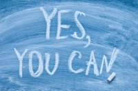 """Motivational message """"Yes you can!"""" written on a chalkboard"""